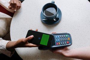 Mujer pagando a través de un teléfono con tecnología NFC