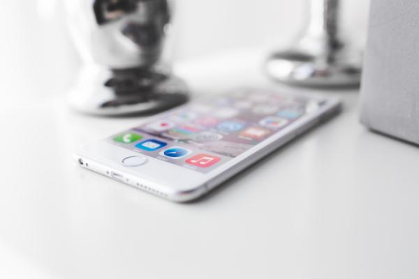 Iphone blanco encima de una mesa con la pantalla iluminada