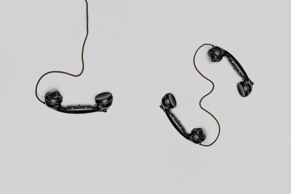Tres teléfonos fijos negros sobre fondo blanco
