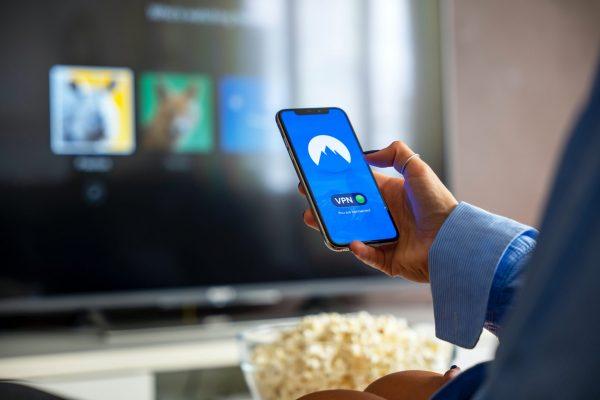Mujer sujetando un teléfono que muestra el VPN activado